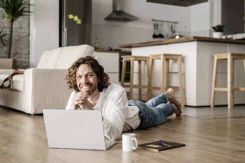Portrait of smiling man lying on the floor at home using laptop - GIOF07515
