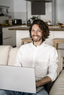 Portrait of smiling man using laptop on couch at home - GIOF07518