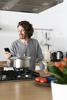 Smiling man using cell phone in kitchen at home - GIOF07530