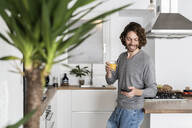 Man holding glass of orange juice and cell phone in kitchen at home - GIOF07533