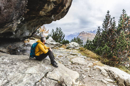Hiker sitting and looking over alpine plateau in autumn, Sondrio, Italy - MCVF00064