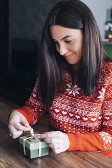 Woman decorating Christmas present - MOMF00803
