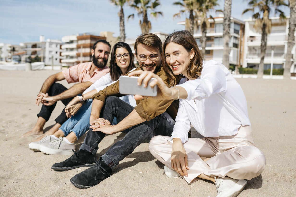 Happy friends sitting on the beach taking a selfie - JRFF03845 - Josep Rovirosa/Westend61