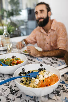 Smiling man sitting at dining table having healthy lunch - JRFF03860