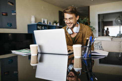 Smiling man working on table at home using laptop - JRFF03869