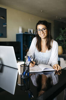 Portrait of smiling woman working on table at home - JRFF03872