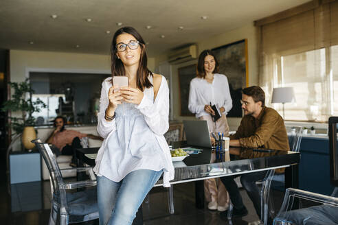 Portrait of woman with cell phone and friends working in background at home - JRFF03890