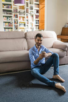 Portrait of smiling young man sitting on the floor of living room at home using smartphone - MGIF00818