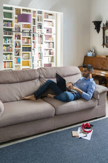 Smiling young man lying on the couch at home using laptop - MGIF00830