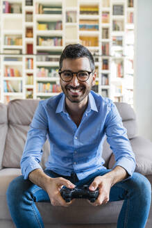 Portrait of laughing young man sitting on the couch at home playing video game - MGIF00839