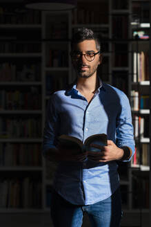 Portrait of young man with book standing in front of bookshelves at home - MGIF00842