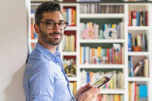 Portrait of smiling young man standing in front of bookshelves at home with digital tablet - MGIF00848