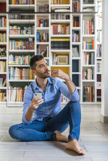 Portrait of pensive young man with smartphone sitting in front of bookshelves on the floor at home looking at distance - MGIF00863