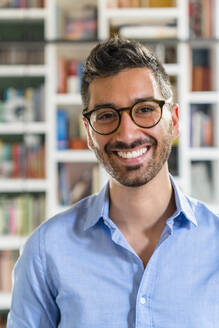 Portrait of laughing young man wearing glasses - MGIF00866