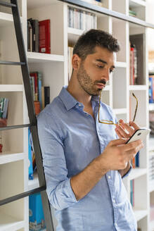 Portrait of pensive young man standing in front of bookshelf looking at cell phone - MGIF00869
