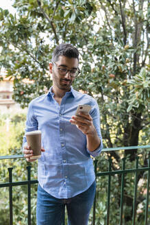 Portrait of young man standing on balcony with coffee to go looking at cell phone - MGIF00875