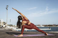 Rear view of Asian woman practicing yoga at harbour - RCPF00084