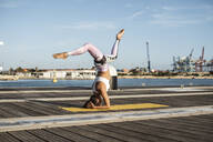 Asian woman practicing yoga on a pier at harbour, headstand with split - RCPF00093