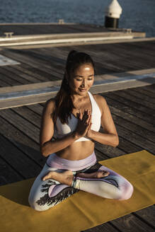 Asian woman practicing yoga on a pier at harbour - RCPF00096