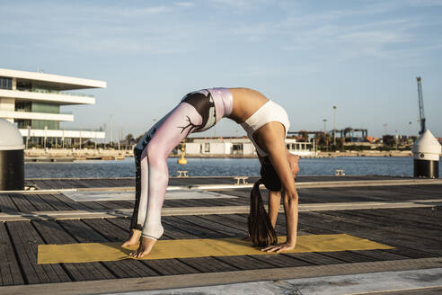 Asian woman practicing yoga on a pier at harbour, upward bow - RCPF00099