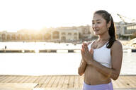 Asian woman practicing yoga at harbour in the evening - RCPF00102