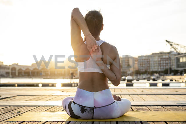 Rear view of Asian woman practicing yoga on a pier at harbour in the evening, cow face pose - RCPF00108 - Rafa Cortés/Westend61