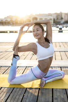 Asian woman practicing yoga on a pier at harbour at sunset, swan pose - RCPF00114