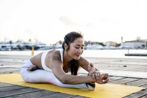 Asian woman practicing yoga on a pier at harbour, seated forward bend - RCPF00117