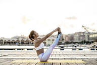 Asian woman practicing yoga on a pier at harbour at sunset, boat pose - RCPF00120