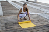 Asian woman practicing yoga on a pier at harbour, rolling out her yellow yoga mat - RCPF00123