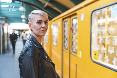Portrait of woman standing at platform, Berlin, Germany - WPEF02246