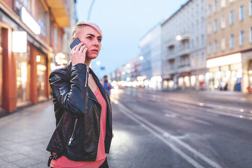 Portrait of blond woman on the phone standing at roadside in the evening, Berlin, Germany - WPEF02255
