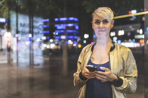 Portrait of blond woman with mobile phone in the city at night, Berlin, Germany - WPEF02261