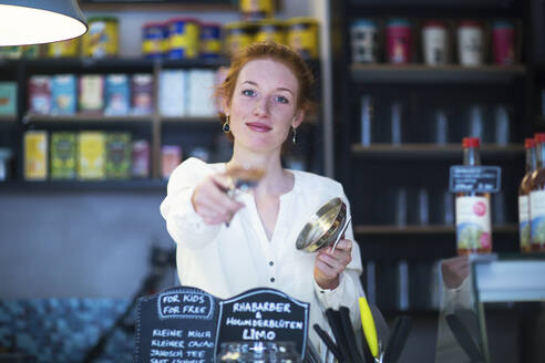 Young woman working in coffee shop - SGF02428
