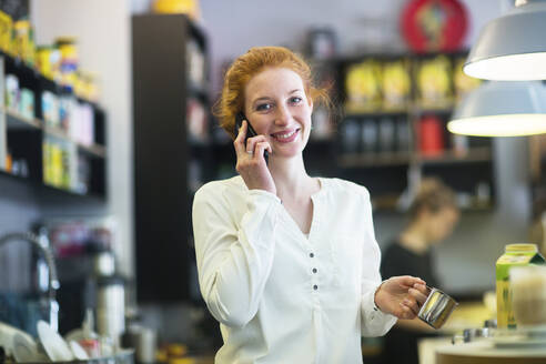 Young woman working in coffee shop, using phone - SGF02431