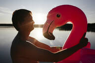Young man with flamingo pool float at sunset - EYAF00652