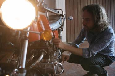 Young man checking his vintage motorbike parked in garage - JPIF00235