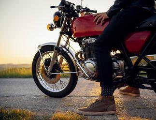 Crop shot of man on his motorbike at sunset, Tuscany, Italy - JPIF00241