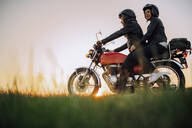 Young couple on vintage motorbike at sunset - JPIF00247