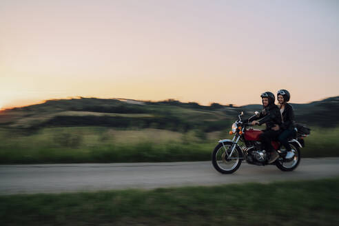 Young couple riding vintage motorbike on country road at sunset, Tuscany, Italy - JPIF00250