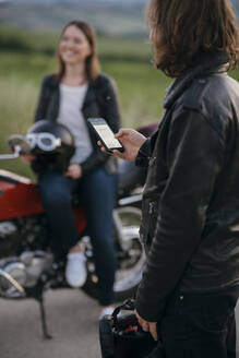 Young motorcyclist standing on country road using smartphone while his girlfriend waiting in the background - JPIF00256
