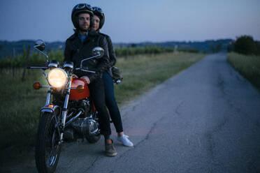 Portrait of young couple on vintage motorbike at roadside - JPIF00259
