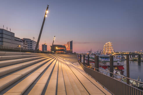 Germany, Hamburg, Steps by river and Elbphilharmonie in distance at dusk - KEBF01411