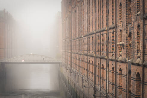 Germany, Hamburg, Speicherstadt, Building and footbridge over canal in fog - KEBF01417