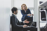 Businesswoman with businessman in office sitting on the floor using laptop - MOEF02528