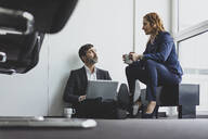 Businesswoman with businessman in office sitting on the floor using laptop - MOEF02534