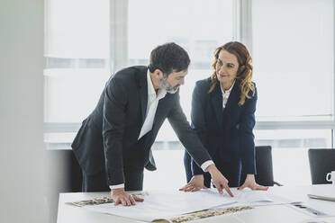 Businesswoman and businessman working on plan on desk in office - MOEF02543
