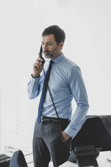 Serious mature businessman on the phone in office - MOEF02546