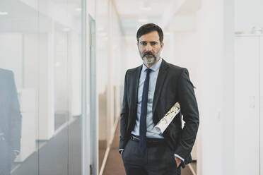 Portrait of serious mature businessman standing on office corridor - MOEF02549