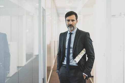 Portrait of serious mature businessman standing on office corridor - MOEF02549